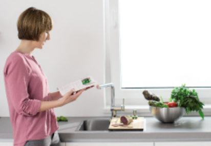 Kjøkkenvask og kran foran et vindu.