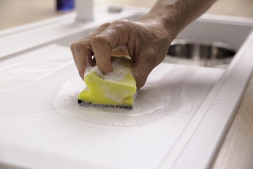 Person som vasker porselensvask med svamp