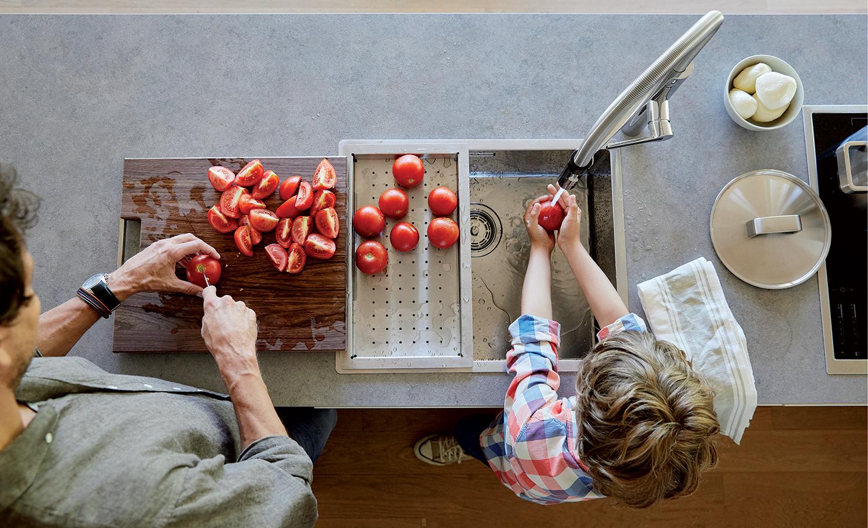 To personer vasker tomater i kjøkkenvask fra Blanco
